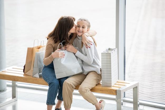 Jovem mãe carinhosa beijando sua linda filha na bochecha enquanto ambas relaxam no banco perto da janela dentro do shopping