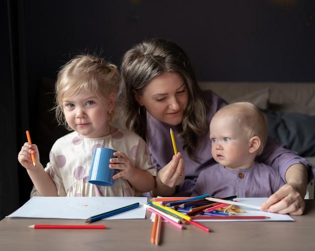 Jovem mãe carinhosa ensinando como desenhar seus dois filhos pequenos
