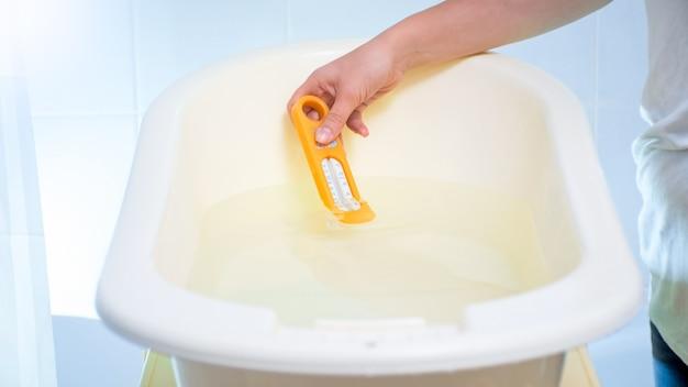 Jovem mãe carinhosa, verificando a temperatura da água com termômetro no banho para o bebê.
