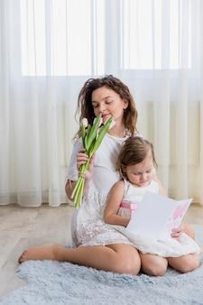 Jovem, mãe, cheirando, flores, enquanto, filha pequena, leitura, cartão cumprimento, casa