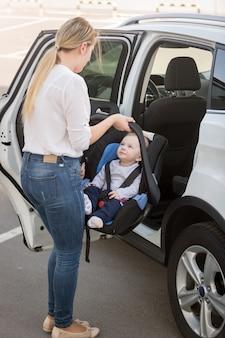 Jovem mãe colocando a cadeirinha com o filho no carro