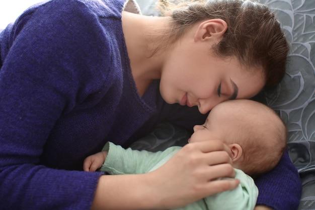 Jovem mãe com bebê dormindo em casa