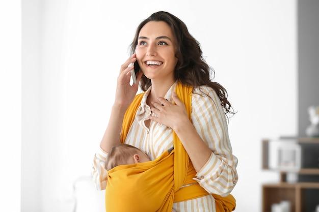 Jovem mãe com bebê na tipóia falando ao celular em casa