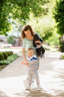 Jovem mãe com dois filhos em uma caminhada no verão
