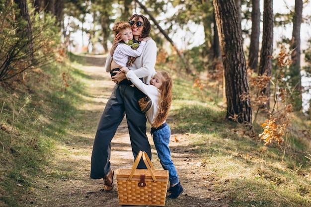 Jovem mãe com filha e filho caminhando para piquenique na floresta
