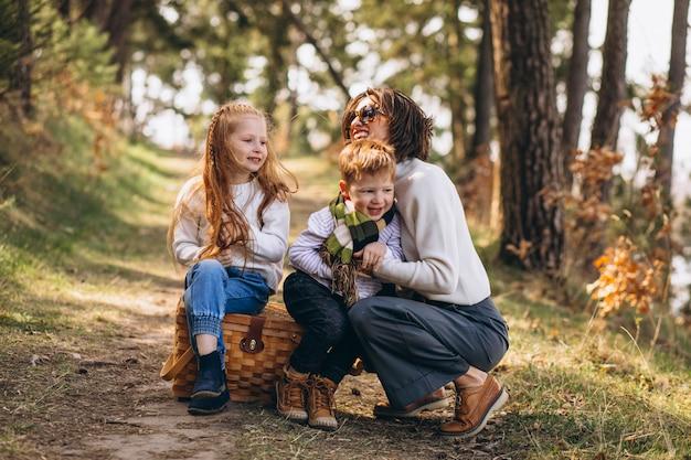 Jovem mãe com filha e filho na floresta