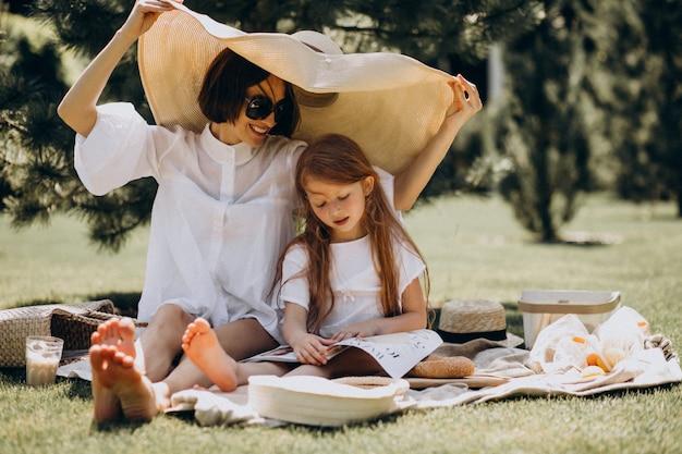 Jovem mãe com filha fazendo piquenique no quintal