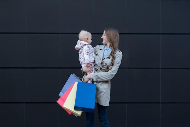 Jovem mãe com filha nos braços e sacos de compras na mão.