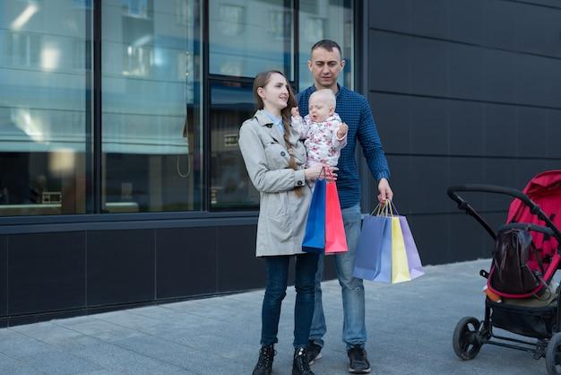 Jovem mãe com filha nos braços. pai com sacolas de compras na mão. compras em família.