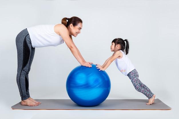 Jovem mãe com filha pequena exercício na bola de fitness