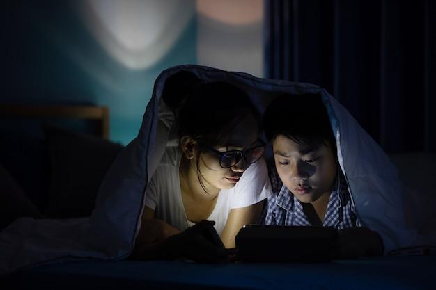 Jovem mãe com filho brincando com um smartphone em uma cama.