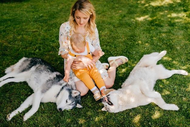 Jovem mãe com filho e dois cachorros sentados na grama