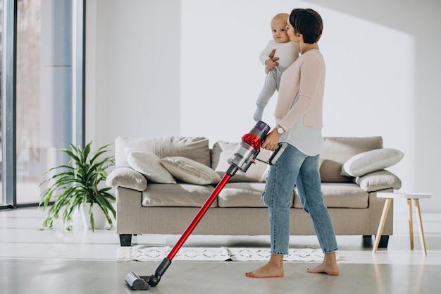 Jovem mãe com filho pequeno limpando a casa