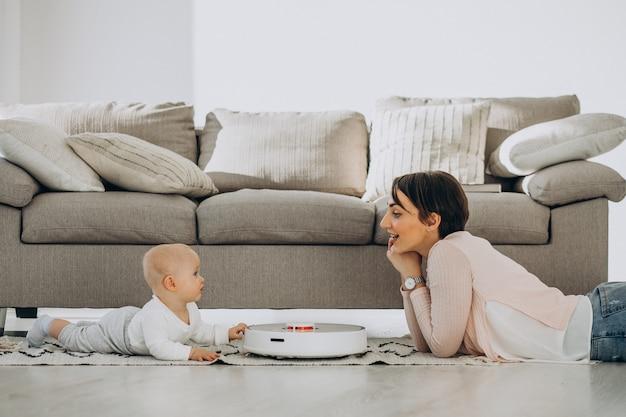 Jovem mãe com filho pequeno observando um robô aspirador de pó fazendo o trabalho doméstico
