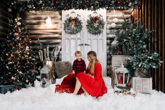 Jovem mãe com filho pequeno perto de árvore de natal