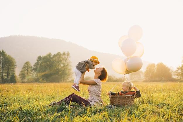 Jovem mãe com filhos com balões na luz do sol ao pôr do sol na natureza ao ar livre