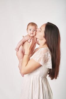 Jovem mãe com maquiagem natural segura o bebê nos braços