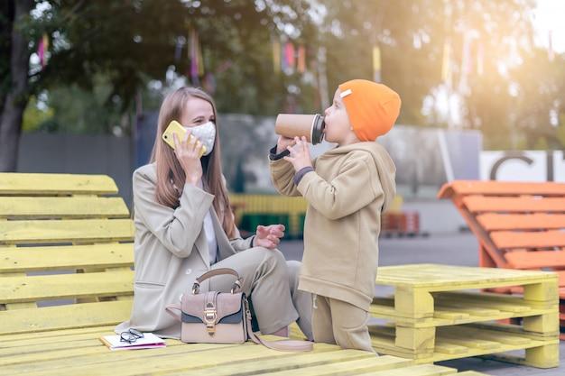 Jovem mãe com máscara médica trabalhando ao ar livre com o filho em idade pré-escolar