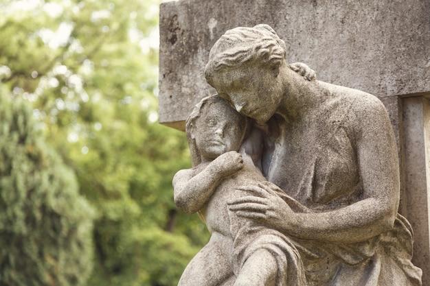 Jovem mãe com monumento de criança pequena em uma tumba em um cemitério