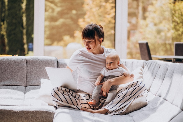 Jovem mãe com o filho dela, trabalhando em casa em um computador