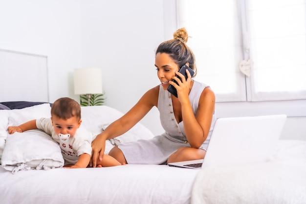 Jovem mãe com o filho no quarto em cima da cama, falando ao telefone