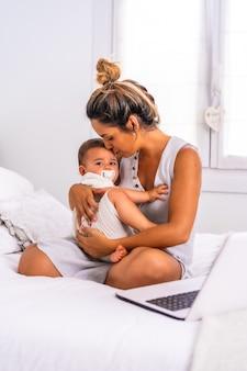 Jovem mãe com o filho no quarto em cima da cama