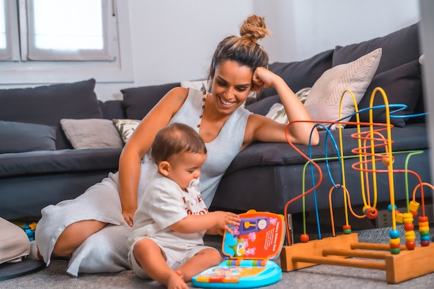 Jovem mãe com o filho sentado no chão ao lado do sofá preto