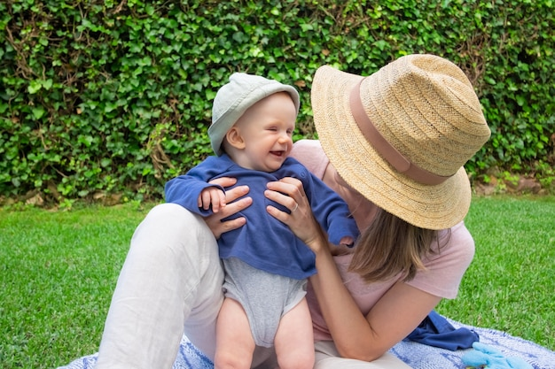 Jovem mãe com o rosto coberto pelo chapéu, segurando a filha