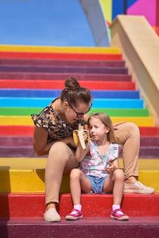 Jovem mãe com óculos e uma filha estão sentados em uma escada colorida. conceito de proteção à criança, dia das mães