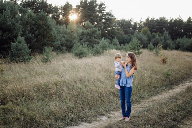 Jovem mãe com seu adorável bebê na floresta