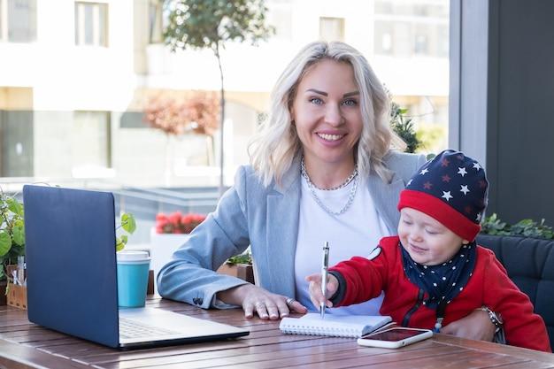 Jovem mãe com seu adorável filho, trabalhando em seu laptop no café ao ar livre.