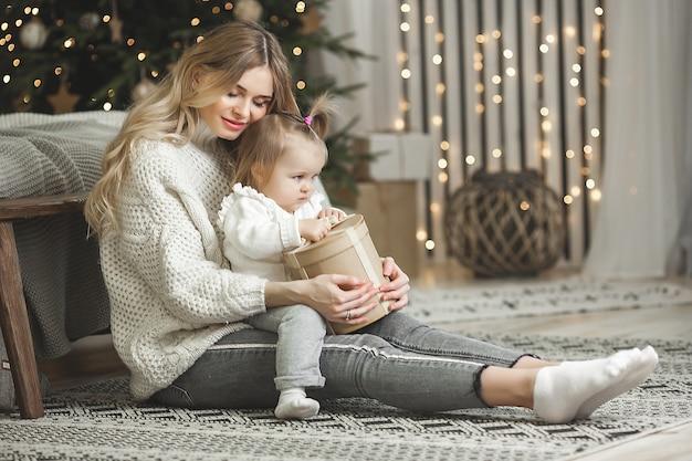 Jovem mãe com seu bebê com decoração de natal