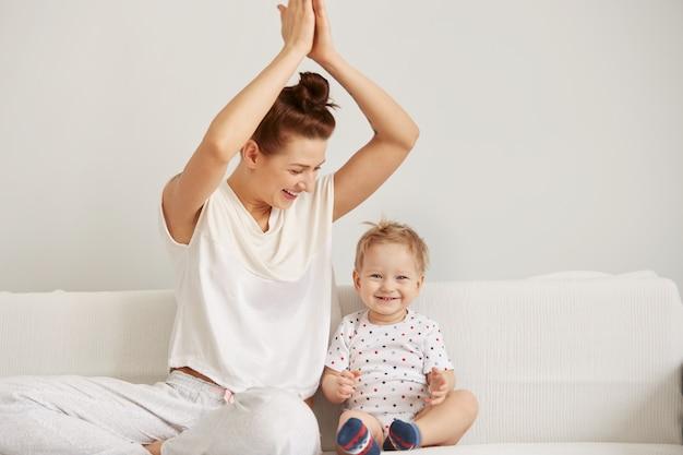 Jovem mãe com seu filho de um ano de idade, vestido de pijama, relaxando e brincando