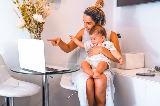 Jovem mãe com seu filho sentado em frente a uma mesa com um computador
