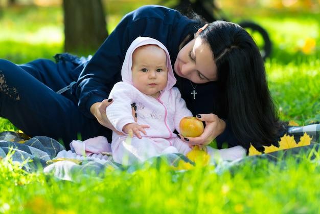 Jovem mãe com seu pequeno bebê em um parque, sentada em um tapete na grama verdejante, oferecendo à criança uma maçã fresca de outono