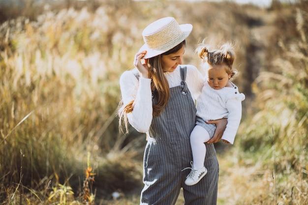 Jovem mãe com sua filha em um campo de outono