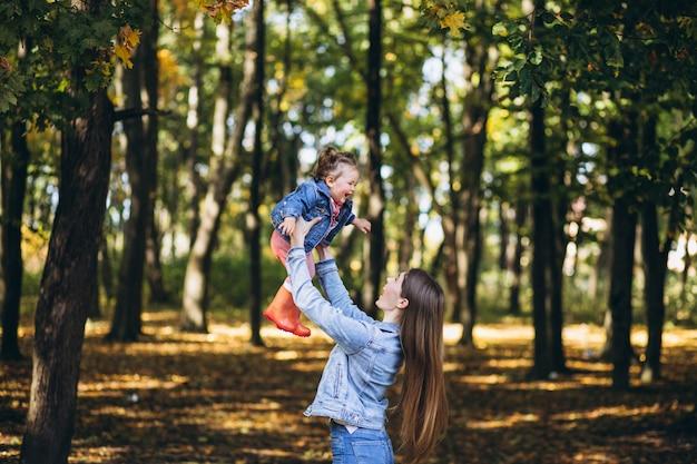 Jovem mãe com sua filha em um parque de outono