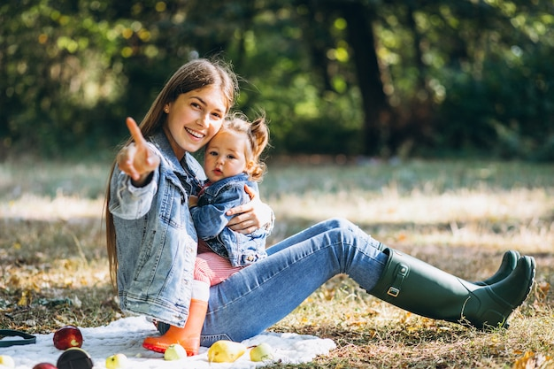 Jovem mãe com sua filha em um parque outono fazendo piquenique