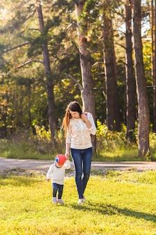 Jovem mãe com sua filha no parque outono.