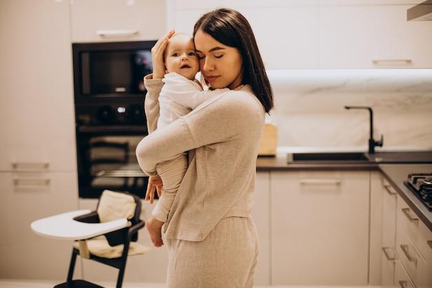 Jovem mãe com sua filhinha em casa