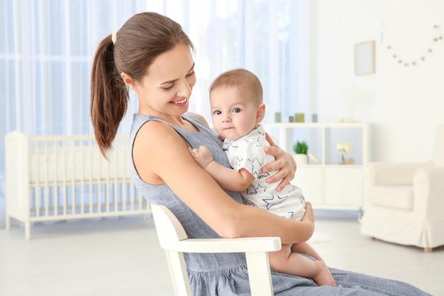 Jovem mãe com um bebê fofo em casa