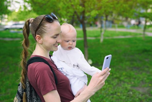 Jovem mãe com um bebê nos braços e usa um smartphone. selfie com uma criança. parque primavera