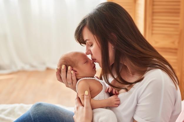 Jovem mãe com um bebê recém-nascido em casa