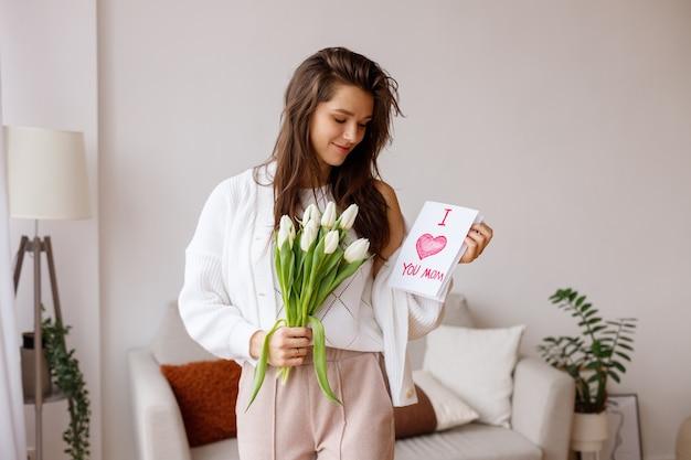 Jovem mãe com um cartão e tulipas na sala de estar