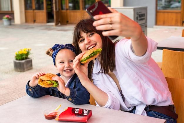 Jovem mãe com uma filha comendo um hambúrguer e tirando uma selfie no café da rua