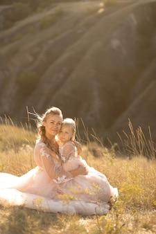 Jovem mãe com uma filha pequena em vestidos cor de rosa estão sentados no campo. mãe abraça a filha, abraçando-a
