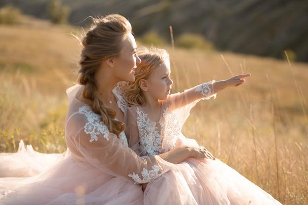 Jovem mãe com uma filha pequena em vestidos rosa estão sentados no campo