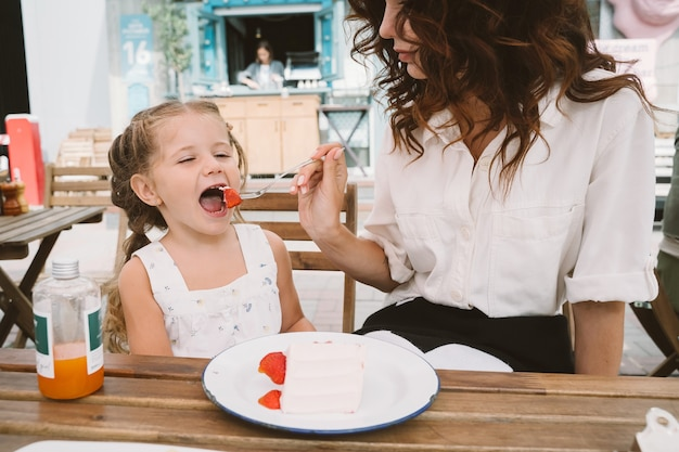Jovem mãe comendo bolo com uma criança sorridente na rua