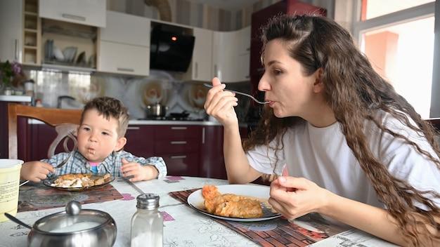 Jovem mãe comendo na cozinha, sentada à mesa.