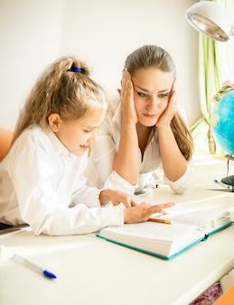 Jovem mãe confusa olhando para o dever de casa da filha